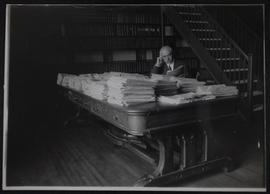 Assistant Saskatchewan Legislative Librarian William H. Munro seated at Confederation Table