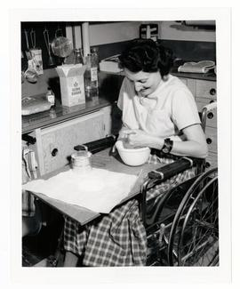 A wheelchair patient using a lap board for mixing cakes, etc