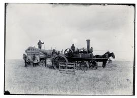 Steam tractor in a field and a man on a rack load of straw