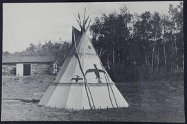 An Indian tepee, a log barn or shed in the back, trees behind the tepee and the barn