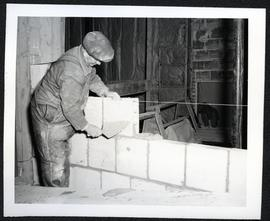 A. Kesthelye laying bricks for a wall in the Shell Oil Building, Regina