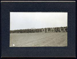 Large body of soldiers marching on parade ground followed by small cannon