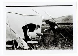 Two men washing up outside tent, on landseekers excursion