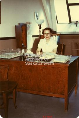 Evelyn Eager at her desk, Saskatchewan Archives office, Field Husbandry Building.
