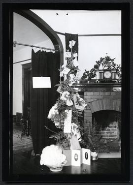 A Christmas tree decorated with small presents, beside a fireplace