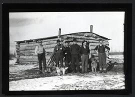 A few men and two dogs in front of a log cabin