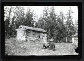 A man sitting on the grass with a dog, small log cabin and trees in background