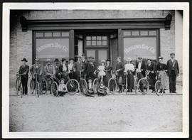 Fort Qu'Appelle Cycling Club standing with their bicycles in front of the Hudson Bay Company store