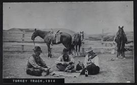 "A ""leisure hour"" at the Turkey Track ranch with three cowboys playing cards in the corral"
