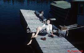 Woman sitting on a dock on Lake Waskesiu