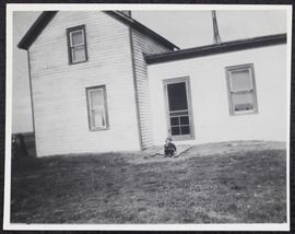 Bert Kinney's house, with Myles Kinney as a small boy on the doorstep