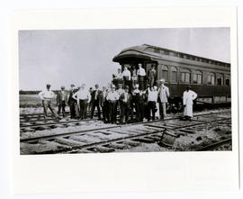 A group of landseekers standing beside a railway car