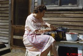Woman in dress peeling potatoes outside a house