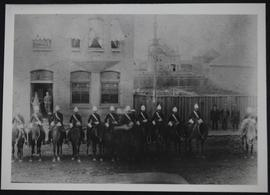 Group of Northwest Mounted Police on horseback with guns and wearing pith helmets