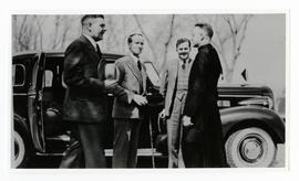 John Buchan, Gov. Gen. Tweedsmuir standing with three unidentified men, one a clergyman, by a car...