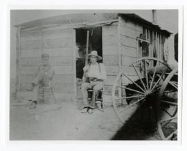 Fred and Charlie White seated outside a homestead shack