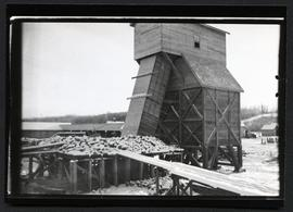 A small granary shaped building with a chute, possibly at a sawmill near Prince Albert