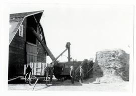 Threshing beside a barn